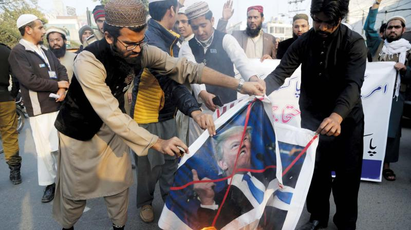 Pakistani protesters burn posters of US President Donald Trump in Lahore.