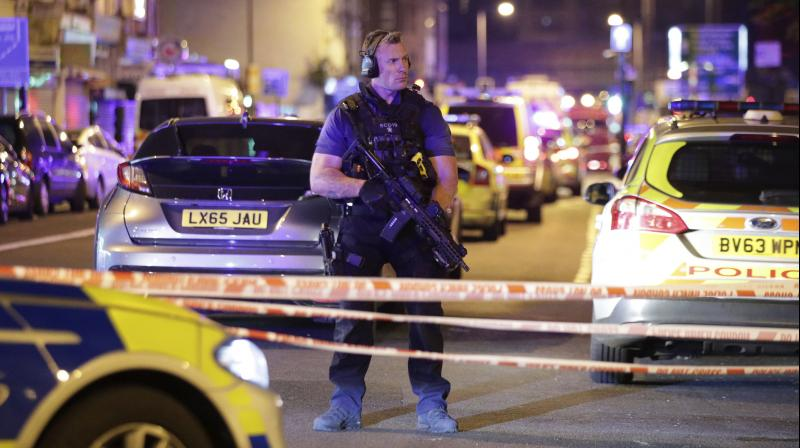 An armed police officer mans a cordon on the Seven Sisters Road at Finsbury Park where a vehicle struck pedestrians in London Monday. (Photo: AP)