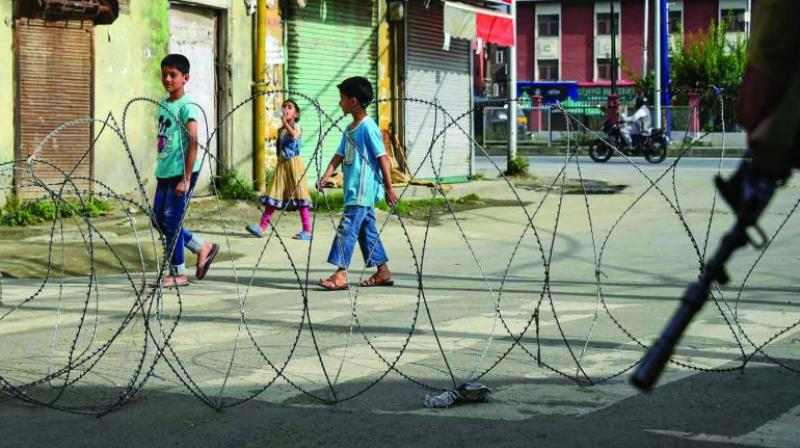Children walk past concertina wire during restrictions following the abrogation of the provisions of Article 370 in Srinagar on Friday. (Photo: PTI)