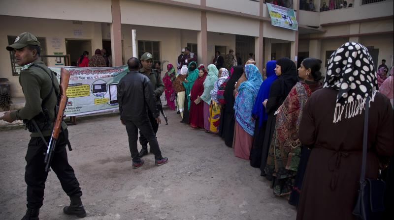 Bangladeshi security personnel stand guard as women line up to cast their votes outside a polling station in Dhaka on Dec 30. (Photo: AP)