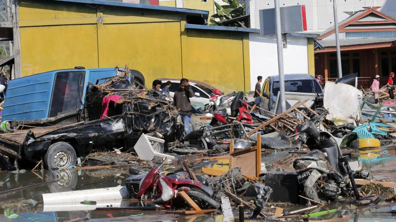 People survey the damage near a shopping mall following earthquakes and tsunami in Palu. (Photo: AP)