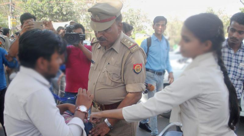 """Anti-Romeo squad of police hauls up a youth in Lucknow on Wednesday. """"Anti-Romeo squads"""" ordered by new Chief Minister of Uttar Pradesh, Yogi Adityanath have started work across the state. (Photo: PTI)"""