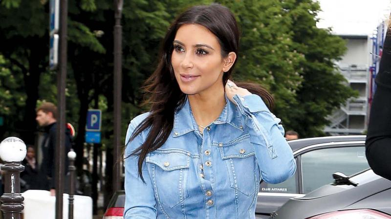 Kim Kardasshian keeps it simple by pairin her outfit with a pair of sunglasses.