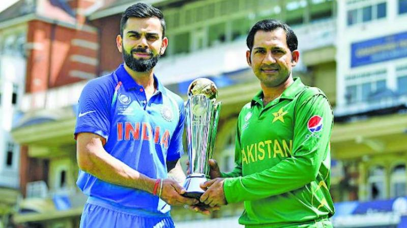 A file photo of India captain Virat Kohli and his counterpart Sarfaraz Ahmed posing with the Champions Trophy. (Photo: AFP)