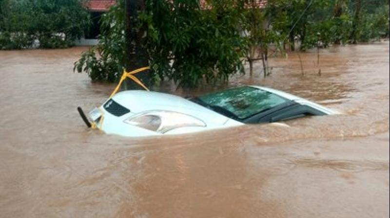 A car is seen submerged in flood water after heavy rainfall, at Vythiri in Wayanad district of Kerala. (Photo: PTI)