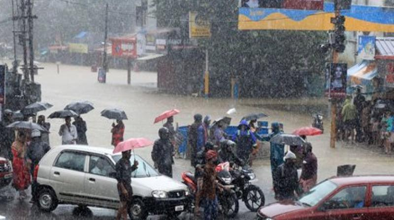 People stranded at a flooded junction following a flash flood, triggered by heavy rains, at Palakkad in Kerala. (Photo: PTI)