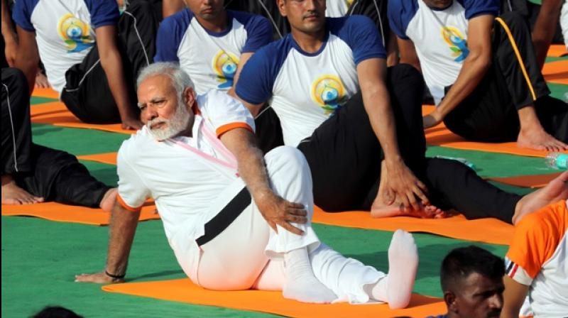 Indian Prime Minister Narendra Modi, front, performs yoga along with thousands of Indians to mark International Day of Yoga in Dehradun, India, Thursday, June 21, 2018.  (Photo: AP)