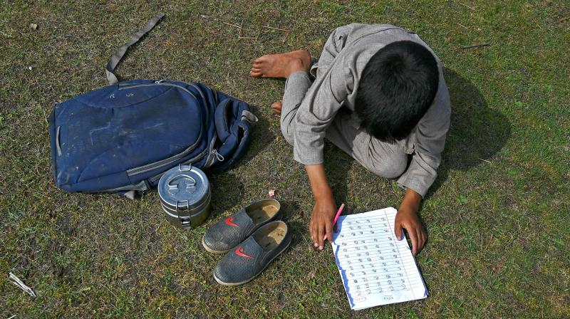 A student attends a class at his open-air school situated on top of a mountain in Doodhpathri, Kashmir. AFP Photo