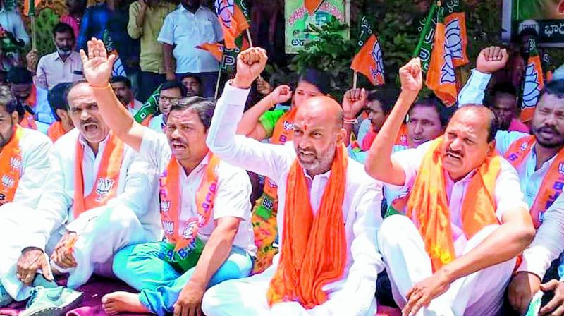 BJP leaders and activists stage a dharna in front of the collectorate in Karimnagar on Monday, demanding that the government solve the Inter Board problems and release ex gratia for the families of the students who committed suicide. They also demanded that the software company responsible for fiasco be punished.  (DC)