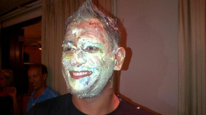 MS Dhoni has his face smeared with cake (Photo: Twitter)