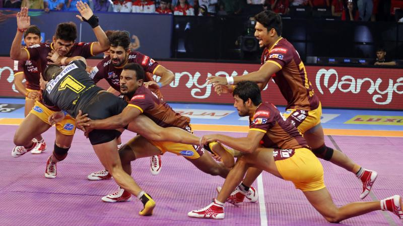 U.P. Yoddha's players make an unsuccessful attempt to pin down Telugu Titans' captain Rahul Chaudhari, in black jersey during the match. (Photo: AP)