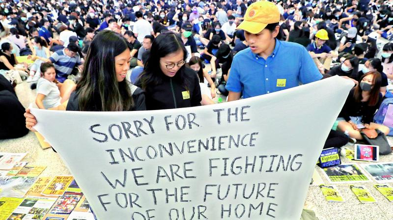 Protesters hold up a banner during a demonstration at the airport in Hong Kong on Friday. (Photo: AP)