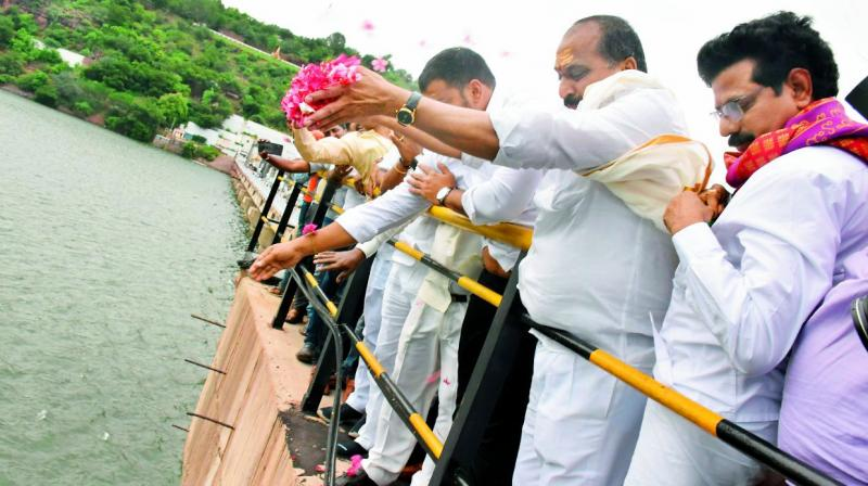 AP and TS ministers perform puja at Sraisalam irrigation project before dam's crest gates were lifted on Friday. (Photo: DC)