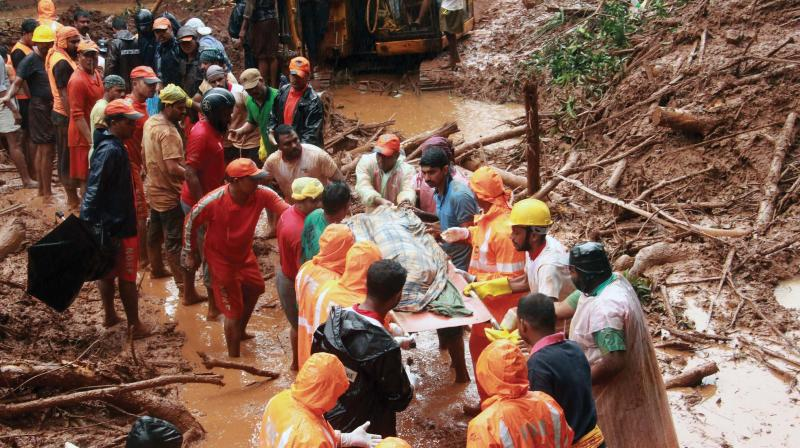 Rescue workers in action at Kavalappara, Malappuram on Saturday where more than 50 persons suspected buried in a landslide. (Photo: DC)