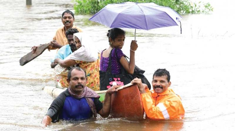 Rescue personnel evacuate local residents in a boat from a residential area at Chengannur in Alappuzha on Saturday. (Photo: PRD)