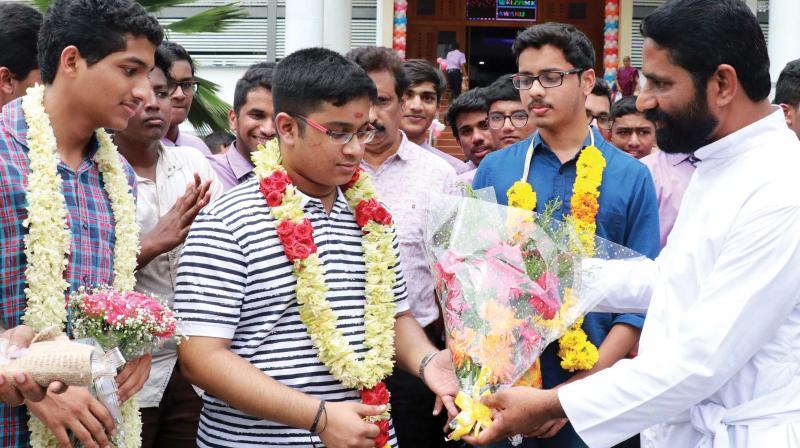 Fr James Mullaseri, principal, KE School, Mannanam, congratulates engineering entrance examination rank holders and the students of the school Goudam Govind (2nd rank), Vishnu Vinod (1st rank) and Mevitt Mathew (5th rank) on Monday.  (Photo: Rajeev Prasad)