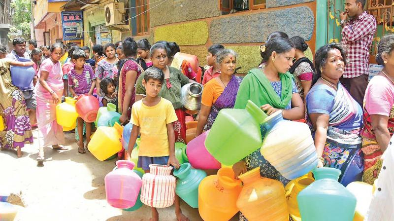 Residents wait for water with empty pots at Vysarpadi in Chennai on Saturday. 	 — DC