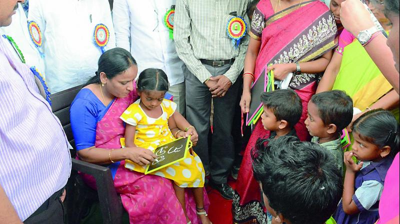 Warangal Rural collector M Haritha performs Aksharabhyasam with a student on Monday. 	—DC