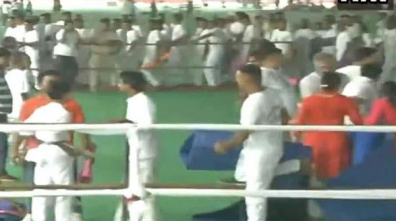 A pandemonium broke out when people started looting yoga mats at the venue where Union Home Minister Amit Shah and Chief Minister Manohar Lal Khattar participated in a yoga programme in Rohtak district of Haryana on Friday. (Photo: Screengrab/ ANI Twitter)