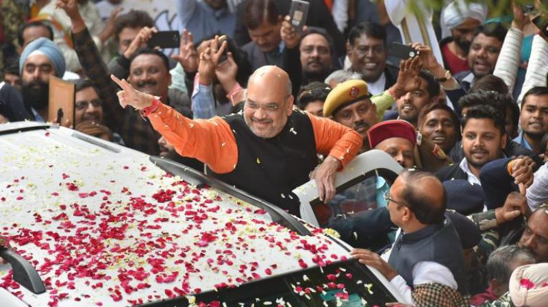 BJP President Amit Shah gestures while being welcomed on his arrival at the party headquarters in New Delhi on Monday, after the party's victory in the Assembly elections in Gujarat and Himachal Pradesh. (Photo: PTI)
