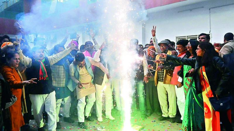 BJP workers celebrate party's victory in Gujarat and Himachal Pradesh Assembly elections, in Lucknow on Monday. 	(Photo: PTI)