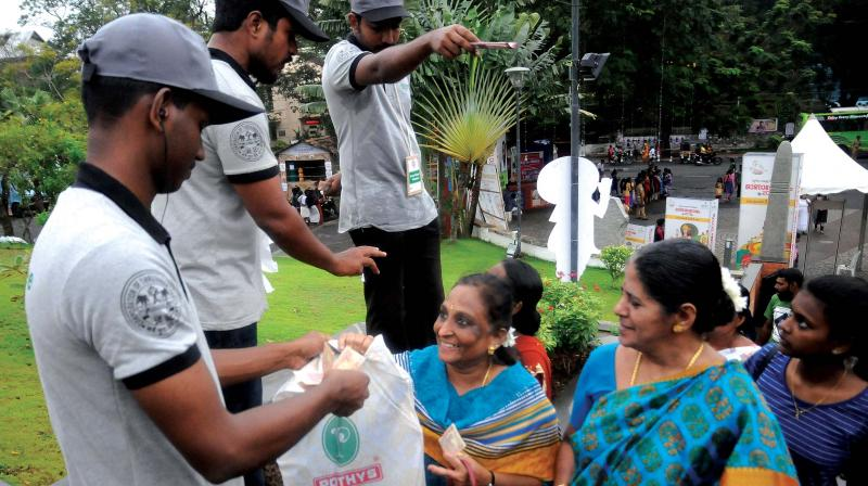 Green Army volunteers put labels on plastic carry bags and bottles, which would be returned to the visitors when they leave Kanakakkunnu ground. A scene on Tuesday. (Photo: A.V. Muzafar)