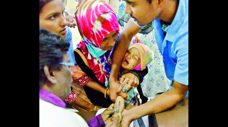 A lab assistant collects blood samples from a child for testing at Gandhi Hospital in Hyderabad on Saturday in view of fast spreading viral fever in the city.  (Photo: Gandhi)
