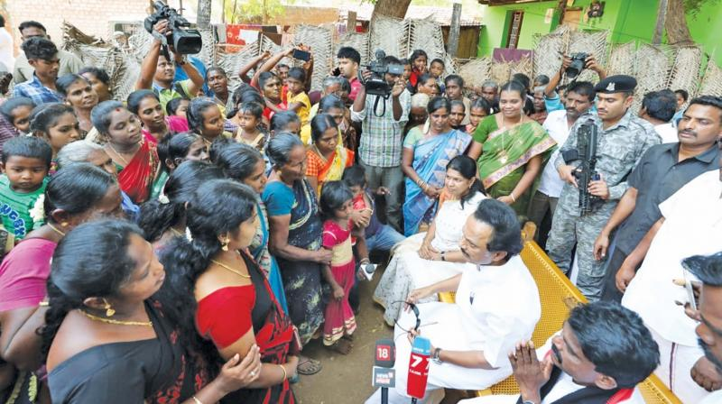 DMK president M K Stalin interacts with the women of Ottapidaram during his  campaign for the Assembly by-election on Tuesday. He was flanked by his sister Kanimozhi and the DMK candidate for the by-poll M. C. Shanmugaiah. 	—DC