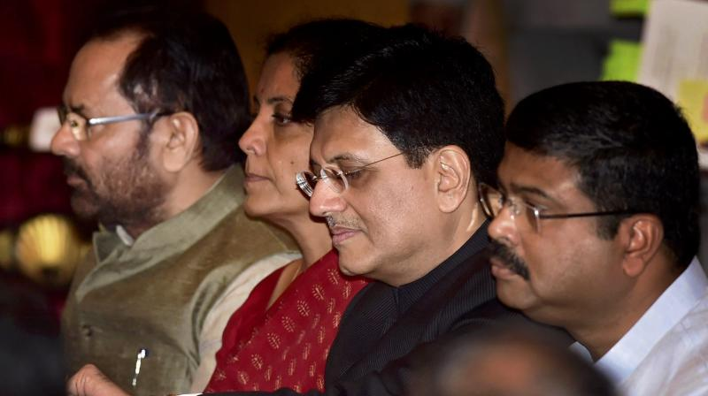 Cabinet Minister Piyush Goyal checks time in his wrist watch as he waits with cabinet colleagues Nirmala Sitharaman, Mukhtar Abbas Naqvi and Dharmendra Pradhan for the swearing in ceremony at Rashtrapati Bhavan in New Delhi on Sunday. (Photo: PTI)