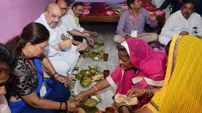 BJP President Amit Shah with Rajasthan Chief Minister Vasundhara Raje having lunch at Dalit Family during his three day visit in Jaipur on Sunday. (Photo: PTI)