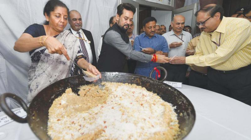 "Union finance minister Nirmala Sitharaman and MoS Anurag Thakur distribute halwa to officials during the ""halwa ceremony"" to mark the beginning of the printing of budgetary documents in New Delhi. (Photo: PTI)"