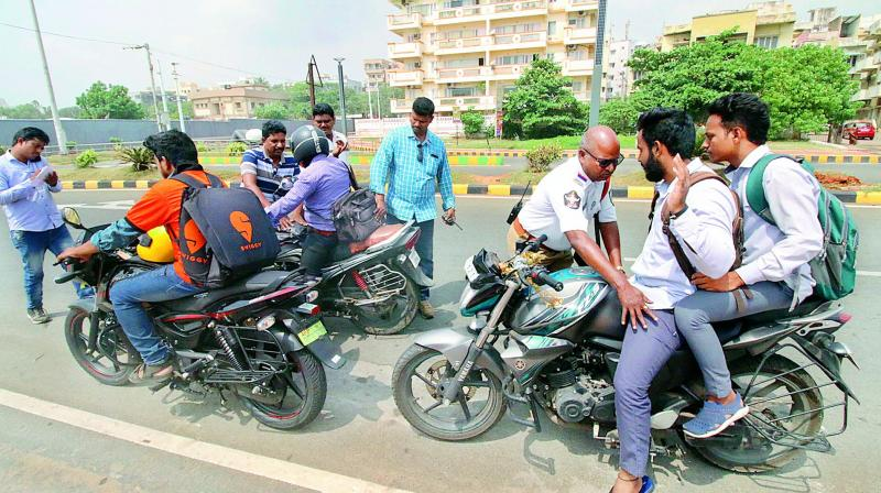 Police personnel inspect the vehicles in the city as many chain snatching cases were reported on Friday morning. (DECCAN CHRONICLE)