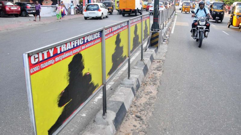 City corporation on Friday blackened the advertisement boards put up by private firms on medians for non-payment of fees. (A. V. MUZAFAR)