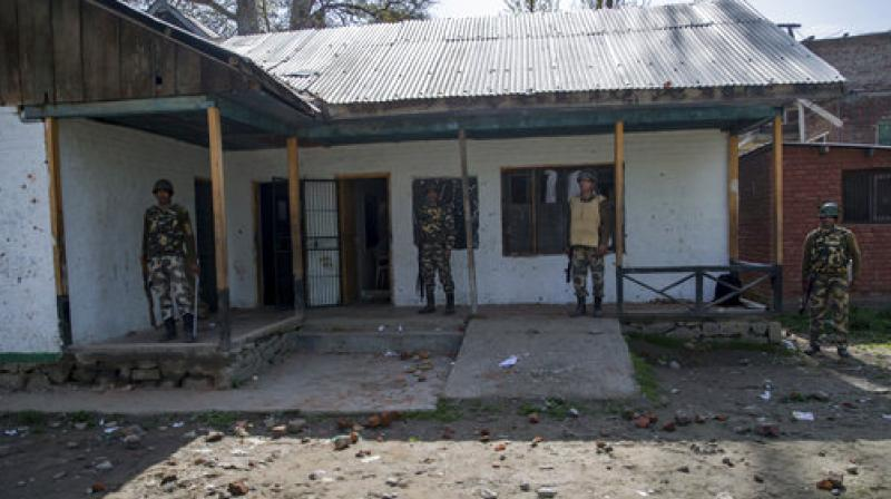 Paramilitary soldiers guard outside a polling station during a re-polling of a by-election for a vacant seat in Dooniwari. (Photo: AP)