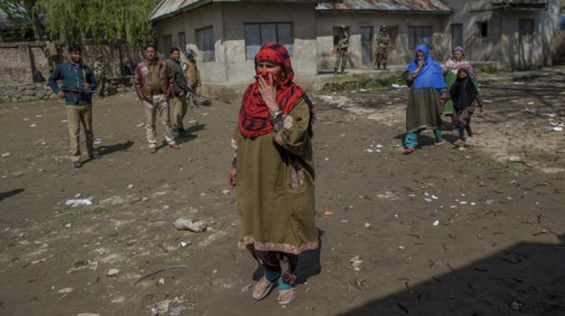 Kashmiri women hide their faces from cameras to conceal their identity as they arrive to cast their votes during a re-polling of a by-election for a vacant seat in Dooniwari. (Photo: AP)