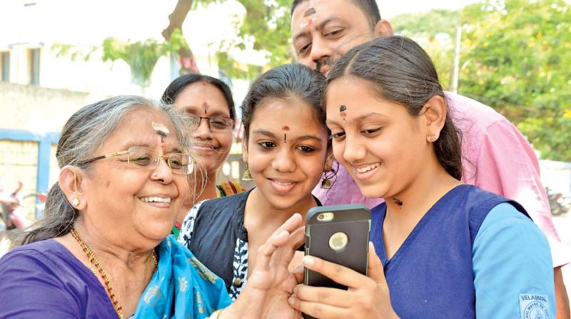 A student shows her results to her grandmother on her phone while the rest of the family looks on in Mogappair on Friday. (Photo: DC)