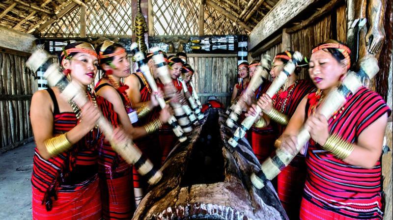 Tribal women play log drum during the Hornbill Festival. Kisama, Nagaland, India.