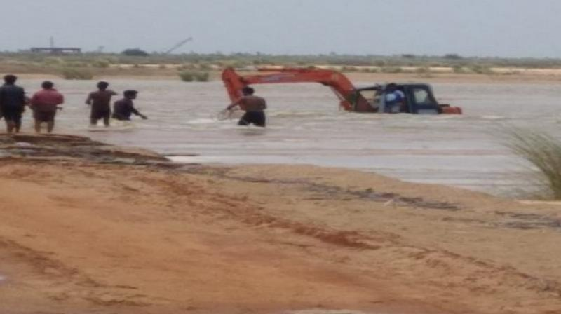 The driver was engaged in work when all of a sudden the water level in Godavari increased and the machine submerged into the river.  (Photo; ANI /Representational)