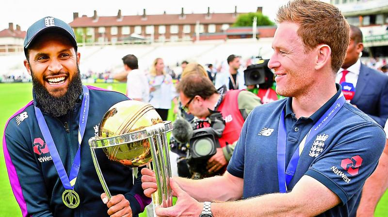 England captain Eoin Morgan (right) and Adil Rashid with the World Cup trophy.  (AFP)