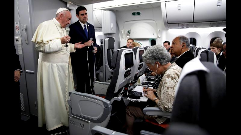Pope Francis, with Vatican spokesman Alessandro Gisotti, answers reporters' questions aboard the plane after taking off from Panama City. (Photo: AP)