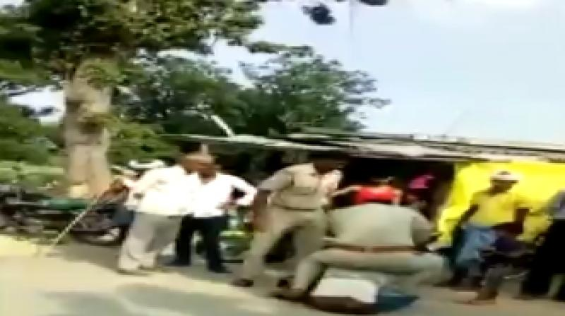 The video which was recorded by a bystander shows sub inspector Virendra Mishra and head constable Mahendra Prasad beating him up and verbally abusing him.  One of them is also seen sitting on him after he is pushed to the ground. (Photo: Twitter | ANI)