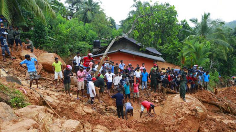 Sri Lankans watch military rescue efforts at the site of a landslide in Bellana village in Kalutara district, Sri Lanka (Photo: AP)