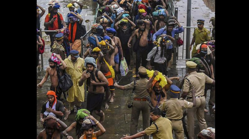 Devotees enter the Sabarimala temple as it opens amid tight security on Friday. (Photo: PTI)