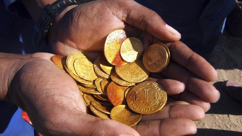 A worker holds gold coins from the wreck of a 16th century Portuguese ship that was discovered in a diamond-mining area on Namibia's Atlantic coast, in Oranjemund. (Photo: AP)