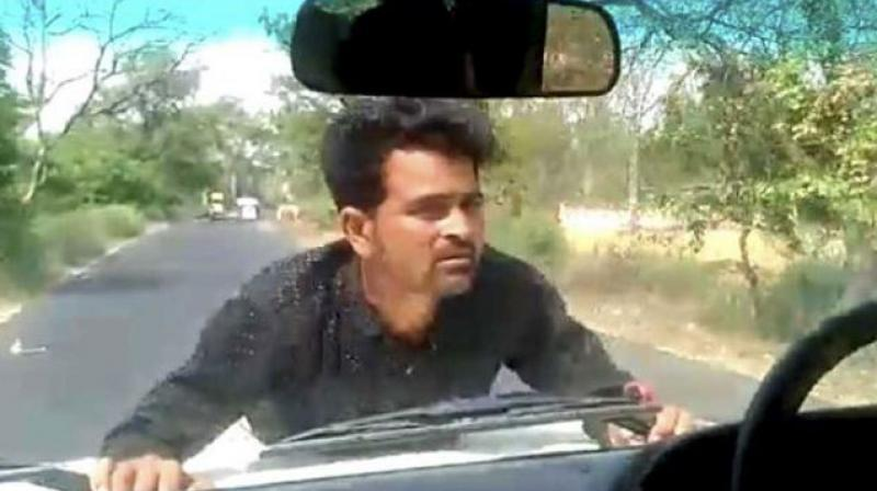 A man clings on to the bonnet of a car in UP's Ramnagar as a block development officer drives for 4 km. (YouTube | Screengrab)