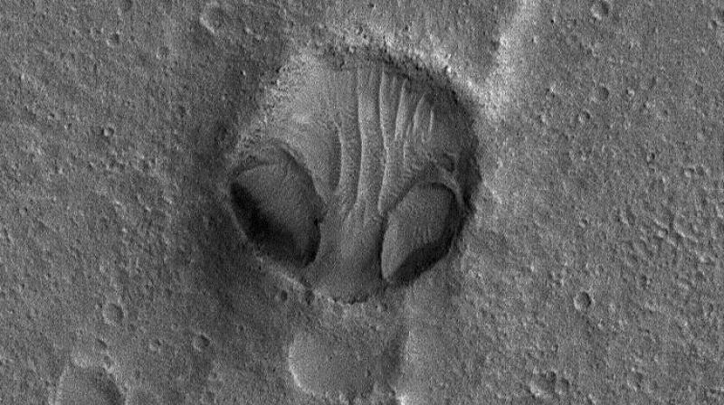 This Mars Global Surveyor (MGS) Mars Orbiter Camera (MOC) image shows an impact crater in Chryse Planitia, not too far from the Viking 1 lander site, that to seems to resemble a bug-eyed head.(Photo: NASA/JPL/Malin Space Science Systems)