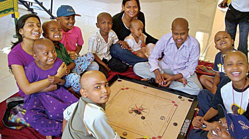 A file photo of volunteers of an NGO with children under treatment for cancer.