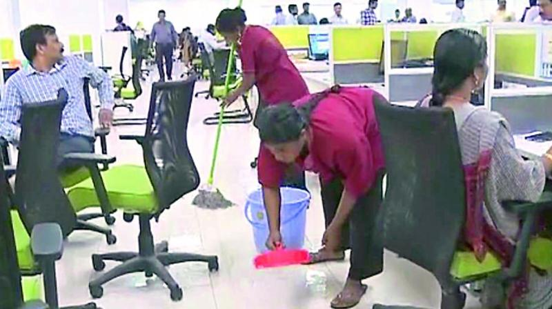 Rainwater being baled out by sanitation staff in the first floor of the AP Temporary Secretariat at Velagapudi of AP capital region on Tuesday. (Photo: DC)