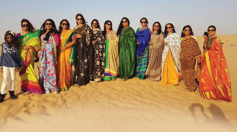 The group proves that sarees are easy to wear by donning them and walking in the sand dunes of Dubai.