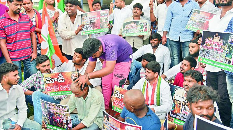 Youth Congress activists tonsure their heads, as they sit in protest at the Ambedkar statue near Tankbund against the police brutality towards students of Banaras Hindu University (BHU) on Monday. (Photo: DC)